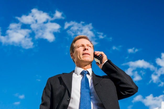 Low angle view of a mature businessman talking on cellphone against sky