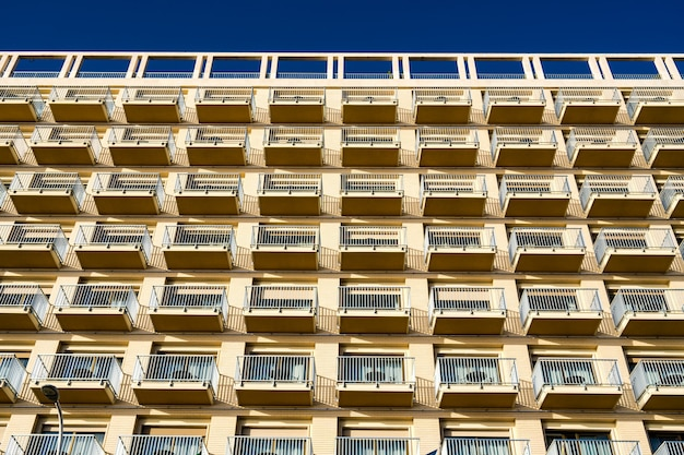 Low angle view of the modern building with balconies against the blue sky