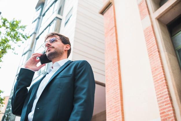 携帯電話で話している建物の下に立っている実業家の低角度のビュー