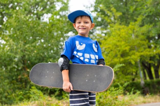 緑豊かな緑の茂みを背景にスケートボードを運ぶハンサムな幸せな誇り高き少年のローアングルビュー