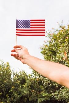 Взгляд низкого угла руки человека показывая флаг сша