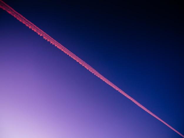 저녁 동안 푸른 하늘에 비행기 트랙의 낮은 각도보기-배경에 적합