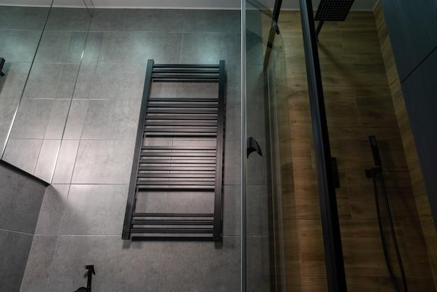 Низкий угол обзора настенного полотенцесушителя в ванной комнате с плиткой под серый цвет и под дерево на стенах