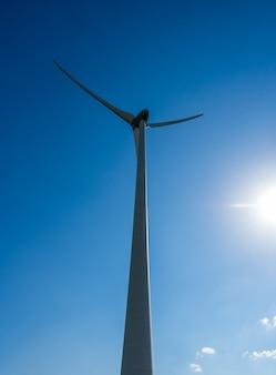 Низкий угол обзора ветряной турбины против неба с облаками