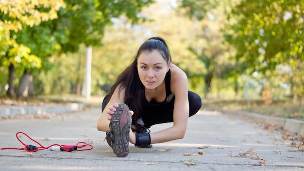 トレーニングとトレーニングのためにウォームアップするときに、脚を路面近くに伸ばしてストレッチする若い魅力的な女性アスリートの低角度ビュー