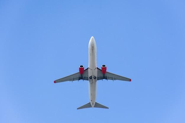 Низкий угол обзора самолета, летящего под голубым небом