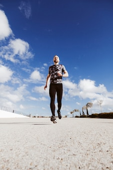 Low angle view of an athletic man running on road