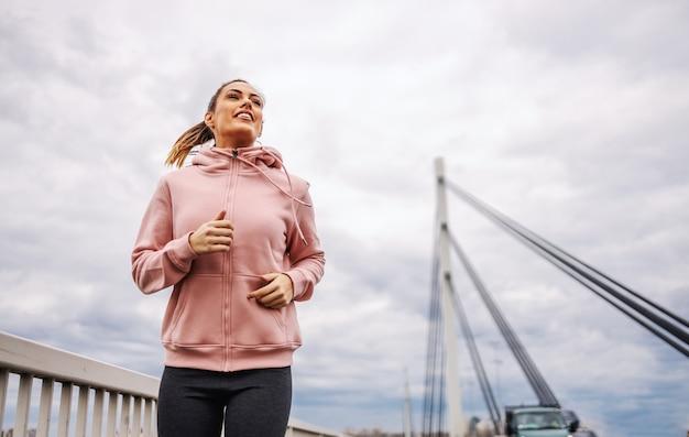 曇りの天候で橋の上をジョギング魅力的なフィットスポーツウーマンの低角度のビュー。屋外フィットネスの概念。
