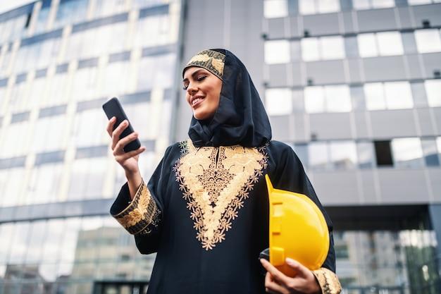 企業の建物の前に立って、スマートフォンを使用して、脇の下の下にヘルメットを保持している魅力的な笑顔のイスラム教徒の女性の低角度のビュー。女性も素晴らしい建築家になることができます。
