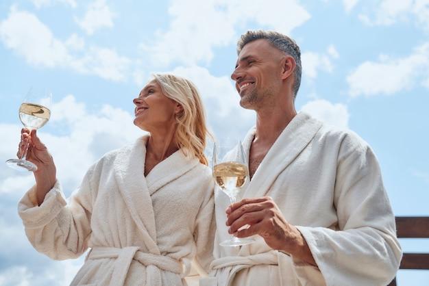 야외에서 휴식을 취하면서 샴페인을 즐기는 목욕 가운을 입은 아름다운 중년 부부의 낮은 각도