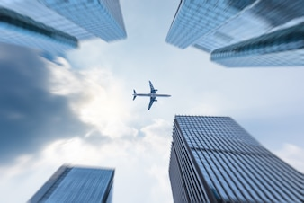 Low angle view of business buildings with plane flying over