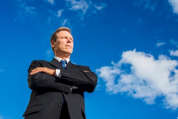 Низкий угол зрения бизнесмена, стоя сложа руки против неба.