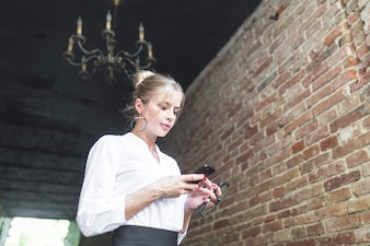 Low angle view of businesswoman using smartphone