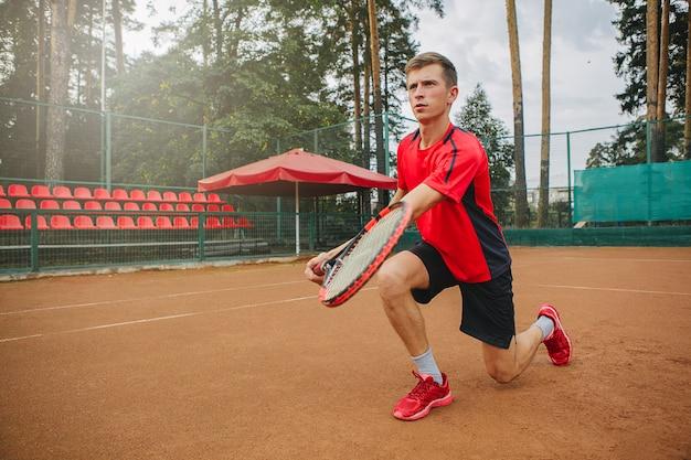 Взгляд низкого угла решительного молодого человека играя теннис