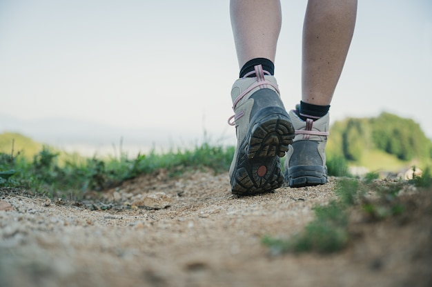 アクティブな旅行中に歩道に立っているハイキングシューズを履いている女性ハイカーのローアングルビュー。
