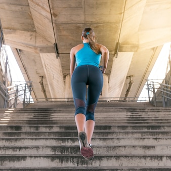 Low angle view of female jogger running on staircase under the bridge