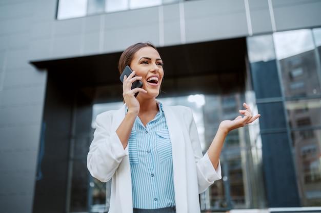 会社の前に立っている間彼女の上司と電話で話している豪華な魅力的な肯定的な笑顔の実業家の低角度のビュー。ミレニアル世代。