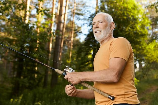 楽しい表情をした濃い灰色のひげを持つハンサムな高齢者60歳の男性の低角度のビュー、湖で釣りをしながら水から魚を引き出し、夏の朝を屋外で過ごす