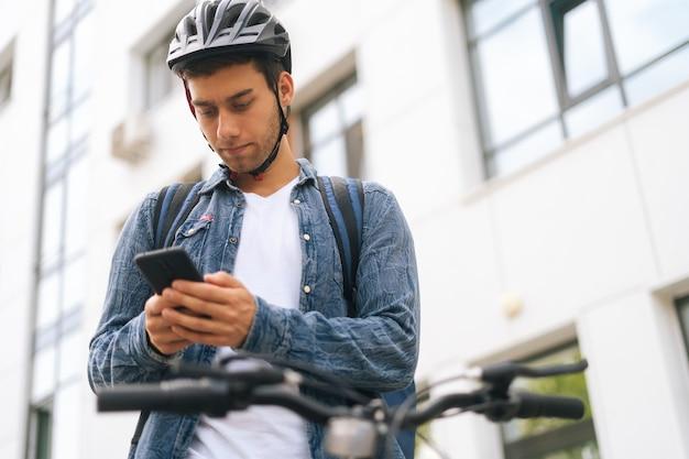도시 거리에서 자전거와 함께 배낭을 메고 전화로 탐색 앱을 사용하는 잘생긴 남성 택배의 낮은 각도 보기, 클로즈업. 스마트폰을 찾고 클라이언트 주소를 찾고 배달 남자입니다.