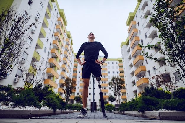 Низкий угол обзора красивого спортсмена с искусственной ногой, стоящего с руками на бедрах на открытом воздухе в окружении зданий.