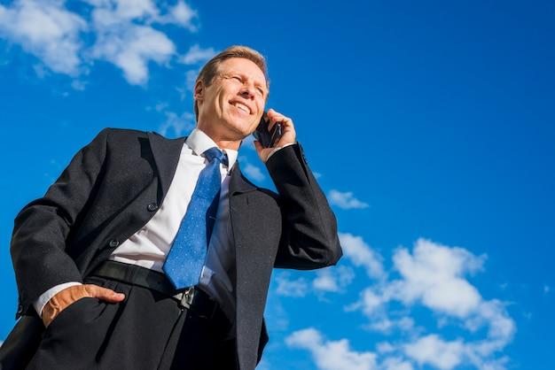 空への携帯電話で話す幸せな実業家の低角度のビュー