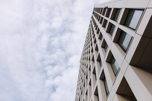 青い空の上の高い近代的な建物のローアングルビュー。高層ビルの外観。アーキテクチャの概念。