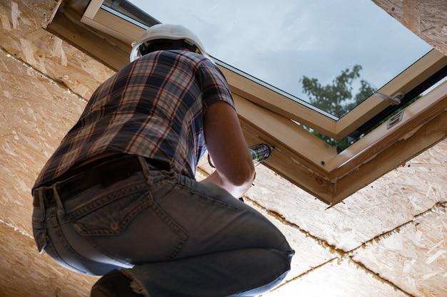 미완성된 집의 천장에 있는 채광창에 신선한 코킹을 적용하는 남성 건설 노동자 빌더의 낮은 각도 보기