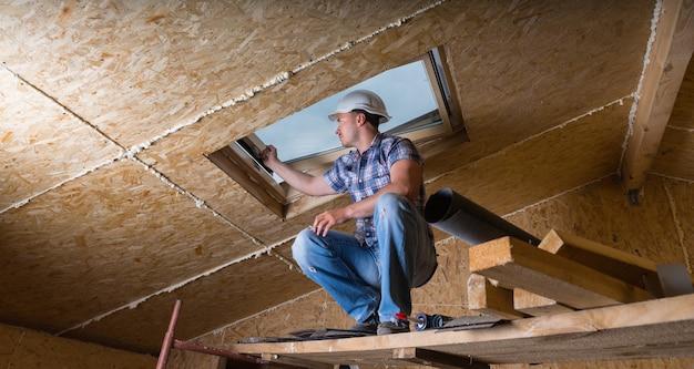 천장 근처의 높은 비계에 웅크리고 있는 남성 건설 노동자 빌더의 낮은 각도 보기 및 노출된 입자 합판 보드가 있는 미완성 집의 스카이 라이트 창 프레임 검사