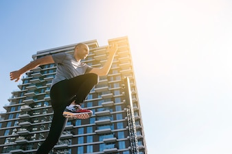 Low angle view of male jogger running in front of building against blue sky