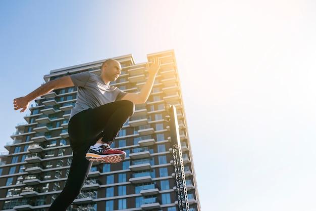 青い空を背景の建物の前で走っている男性のジョガーの低角度のビュー