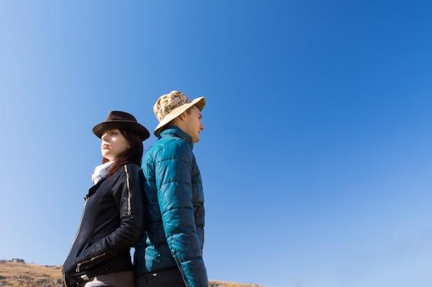 青い空を背景に屋外で背中合わせに立っている男性と女性のローアングルビュー Premium写真