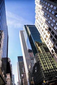 미국 뉴욕시 유리벽에 반사된 맨해튼 고층 빌딩의 낮은 각도 보기