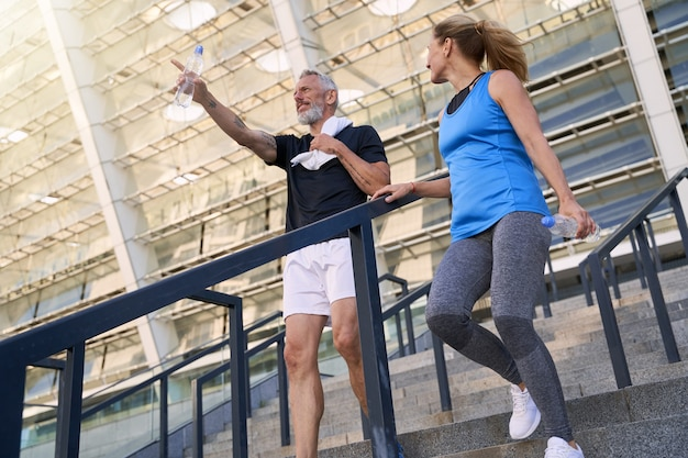 Низкий угол обзора зрелой пары, мужчины и женщины в спортивной одежде, спускающихся по лестнице после работы