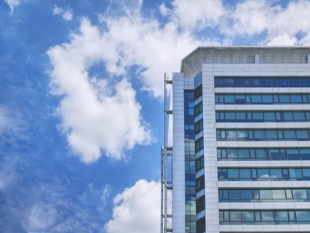 흐린 하늘을 배경으로 왼쪽에 배관 시스템이있는 현대식 건물의 낮은 각도보기