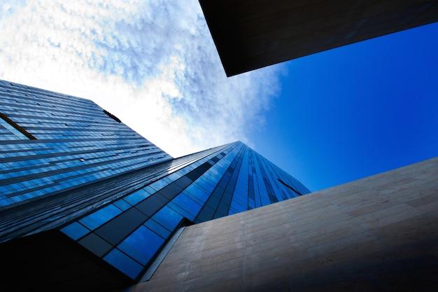 낮에는 햇빛과 푸른 하늘 아래 현대적인 고층 빌딩의 낮은 각도보기