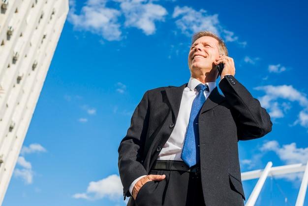 携帯電話で話す笑顔の成熟したビジネスマンの低角度のビュー