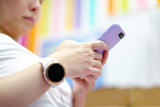 스포츠웨어 여성의 낮은 각도 보기는 복사 공간이 있는 가정 실내 운동 에어로빅 후 앉아서 스마트폰을 사용합니다.