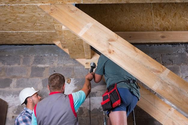 미완성된 새 집에서 나무 계단 프레임을 구축하는 건설 노동자 팀의 낮은 각도 보기