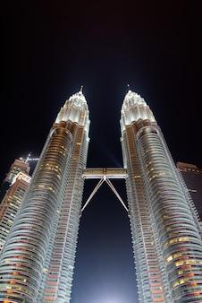 マレーシア、クアラルンプールの夜の有名なペトロナスタワーのローアングルビュー垂直ショット