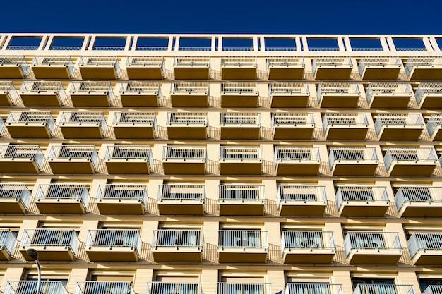 푸른 하늘을 배경으로 발코니가있는 현대적인 건물의 낮은 각도보기