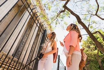 Low angle view of two female friends standing outside the gate looking at the columns