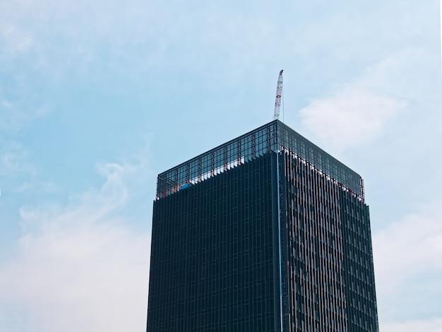 空を背景に屋根の床にクレーンで建設中の建物のローアングル ビュー