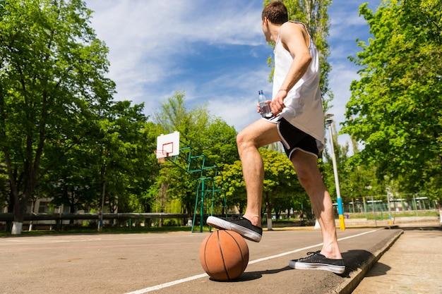 농구 코트의 옆 라인에 서 있는 젊은 운동 남자의 낮은 각도 보기