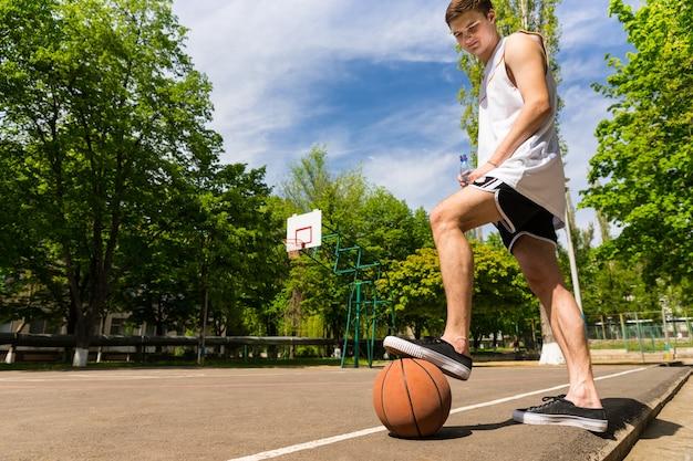농구 코트의 옆 라인에 서 있는 젊은 운동 남자의 낮은 각도 보기 공 위에 발이 구르는 것을 방지