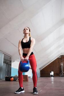 Низкий угол обзора молодой кавказской спортсменки в спортивной одежде, делающей упражнения с гирями в старом тренажерном зале