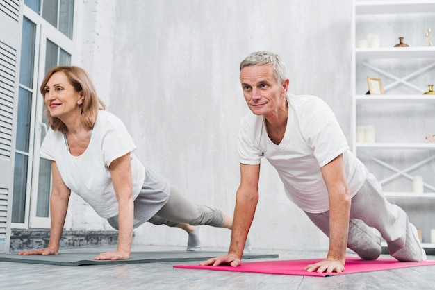 Low angle view of old couple doing pushups on mat at home