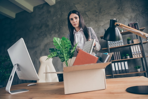 Low angle view photo of frustrated girl collar put keyboard in cardboard box quit office marketer occupation company crisis bankrupt wear blazer jacket suit in workplace workstation