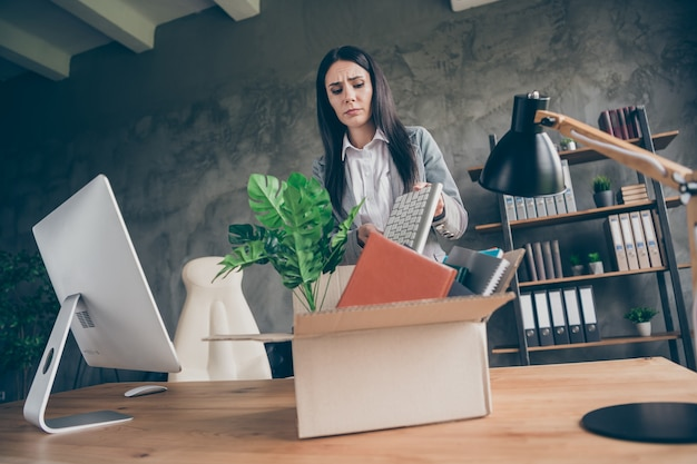 Low angle view photo of frustrated girl put keyboard in cardboard box cry dont want quit job company bankrupt corona virus crisis wear blazer jacket in workstation loft