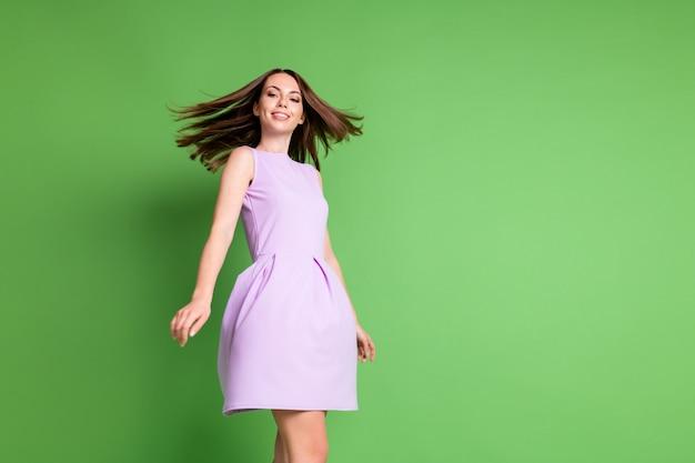 Низкий угол обзора фотография жизнерадостной молодой девушки леди зубастая улыбка танцевальная вечеринка выпускного вечера ночной клуб расслабляющее вращающееся движение платье для волос ударная одежда фиолетовый наряд изолированный пастельный зеленый цвет фона