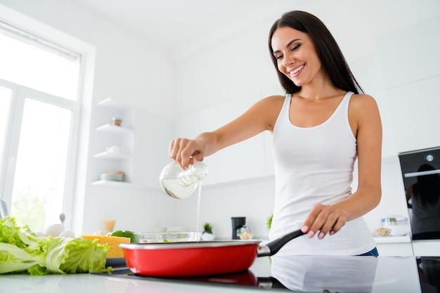 긍정적 인 명랑 소녀 진짜 요리사의 낮은 각도보기 사진은 프라이팬에 맛있는 미식가 저녁 식사를 요리하고 나머지는 부엌 집에서 휴식을 취합니다